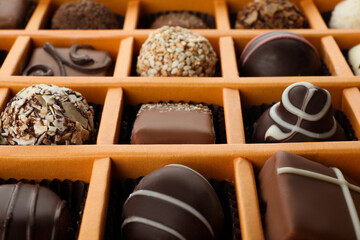 Box with different chocolate candies as background, closeup