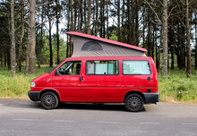 Red Van With Roof Up. Campervan Parked Next To Forest.