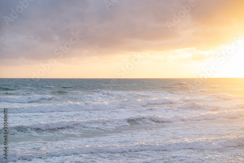 Mare Jonio moved, Puglia, South Italy, the waves agitated by the wind of Scirocco foam as they approach the shore, the large clouds are colored orange in the golden hour of sunset Canvas Print