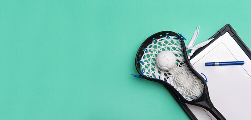 Lacrosse stick, ball and tactical board with marker on green background. Sport coach concept