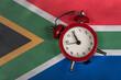 canvas print picture - National flag of Republic of South Africa and vintage alarm clock, close up.
