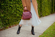 Detail Of Young Fashionable Woman Wearing Beige Wool Coat, Tulle Midi Skirt And Black High Heel Cowboy Boots. She Is Holding Stylish Burgundy Handbag In Hands. Street Style.