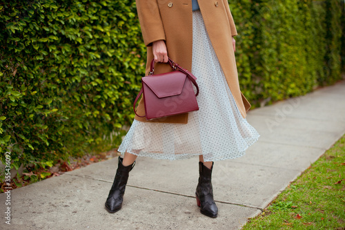 Fotografia Detail of young fashionable woman wearing beige wool coat, tulle midi skirt and black high heel cowboy boots