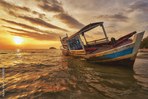 Beached fishing boat during sunset at Otres beach in Sihanoukville Wallpaper Mural
