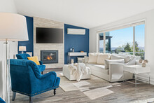 Welcoming Living Room With A Blue Accent Wall, White Faux Fur Pillows And A Modern Fireplace