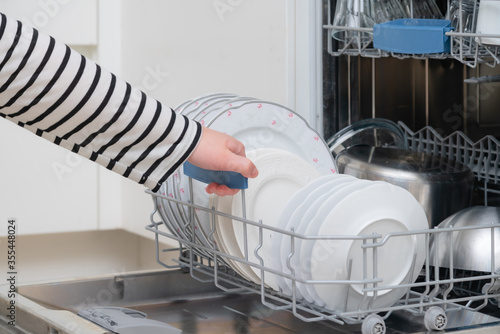 Close up of hand unloading dish washer in the kitchen Fotobehang