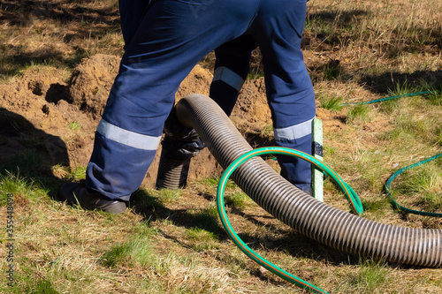 Foto Man worker holding pipe, providing sewer cleaning service outdoor