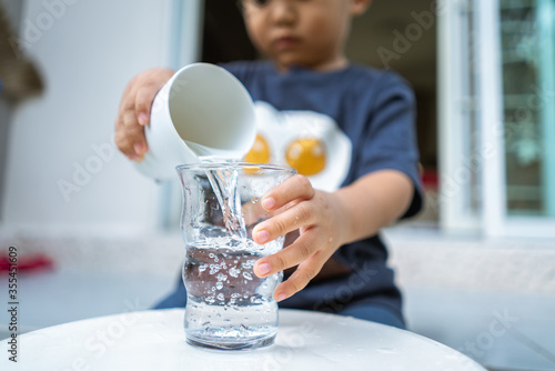 little kid playing and pouring water to glass Wallpaper Mural