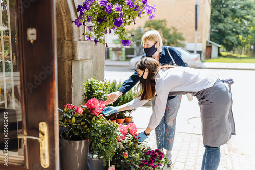 Young woman florist helping female client to choose potted plant in flower shop Canvas-taulu