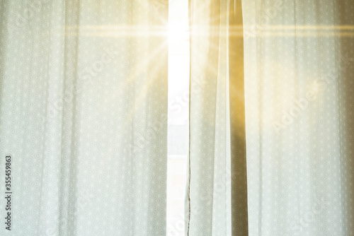 Obraz the window with curtains and a sun beam go through, wake up, early morning time - fototapety do salonu