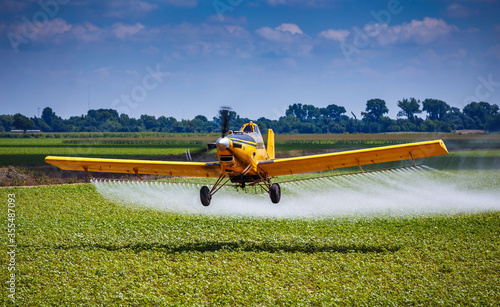 Photo Yellow Crop Duster Airplane Aerially Applies Pesticide to Cotton Fields in Texas