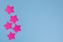 Five Bright Pink Stars Stickers On A Blue Background. Flat Layout With Copy Space