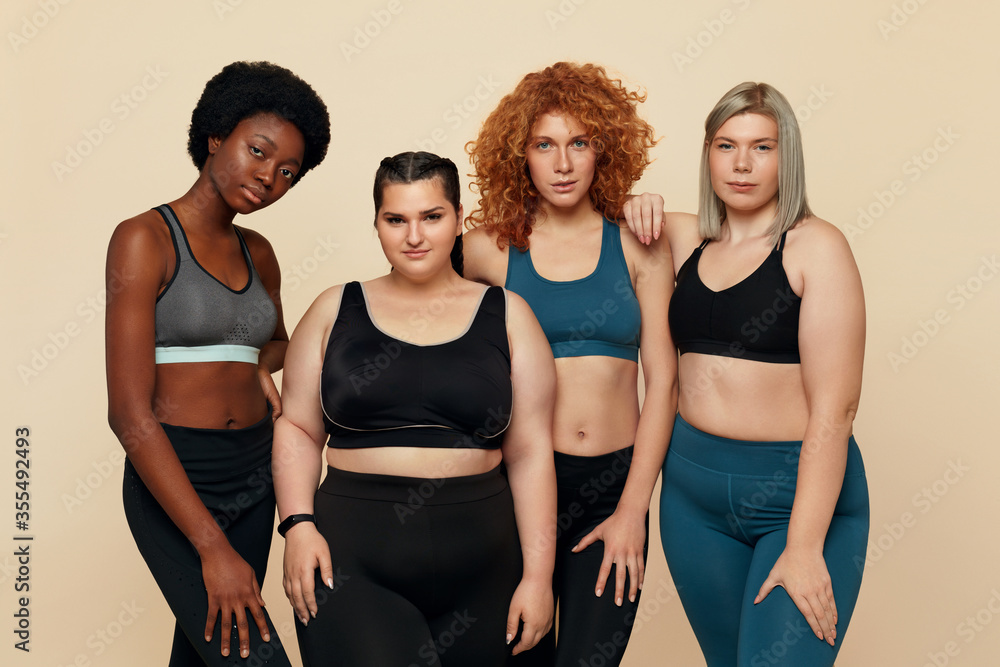 Fototapeta Diversity. Group Of Models With Different Figure Size And Body Types Portrait. International Friends In Sportswear Posing On Beige Background. Body Positive As Lifestyle.