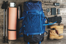 Backpack And Hiking Equipment On Wooden Background, Top View