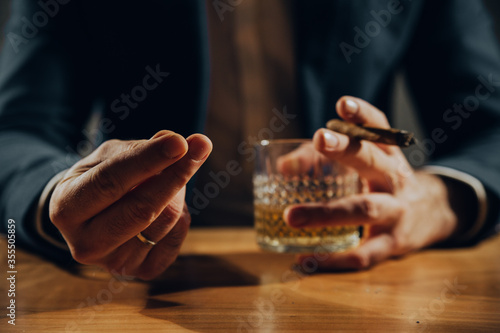 Fotografía Close up of man playing card and drinking whisky.