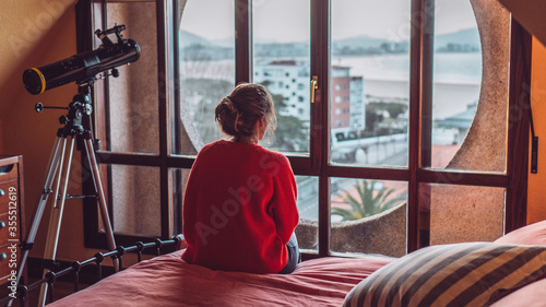 Girl looking through the window of her room sitting on the bed Fototapeta