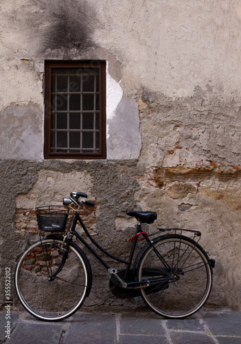 An old bicycle with metal basket rests against a weathered cement wall in Lucca, Italy