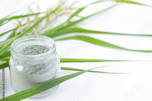 Obraz na plátně Green clay in a glass jar on a white table with green grass