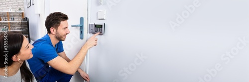 Photo Handyman Installing Security System Near Door Wall