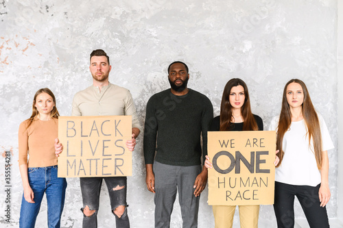 Fototapeta A protest against cruelty and racism. Multi-racial group of young people with signs