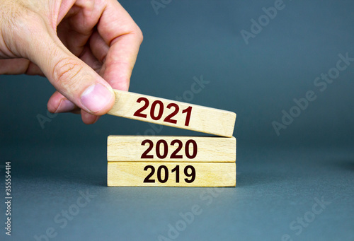 Fototapety, obrazy: A male hand stacks wooden blocks with numbers 2019, 2020, 2021.