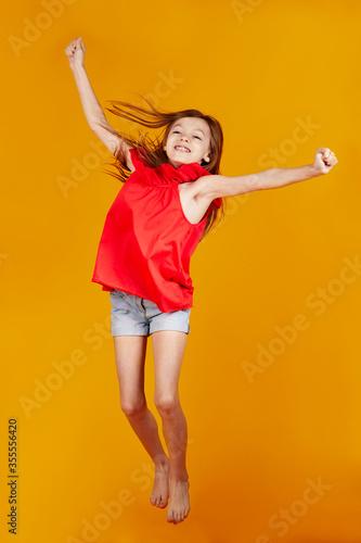Photo jolie jeune enfant fille caucasienne aux cheveux longs châtains sautant de joie
