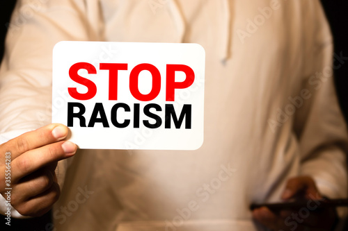 Man holding cardboard banner with STOP RACISM message Wallpaper Mural