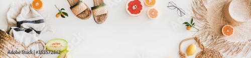 Obraz Summer mood layout. Flat-lay of natural espadrillas and sandals, straw sunhat, beach rafia and net bag, towel, sunglasses and fruit over white plain background, top view, copy space, wide composition - fototapety do salonu