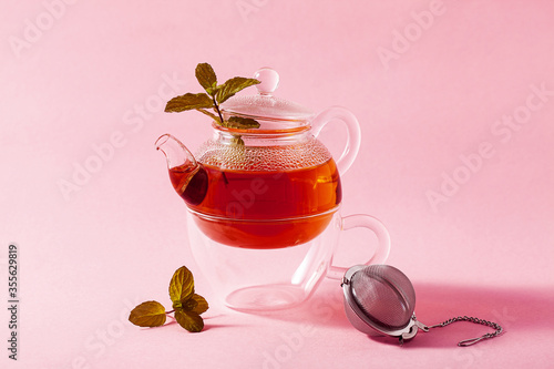 Obraz na plátne tea in a glass teapot on a pink background and a metal Infuser Filter