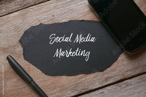 Fototapety, obrazy: Top view of a pen,mobile phone and a piece of black torn paper written with Social Media Marketing on wooden background.
