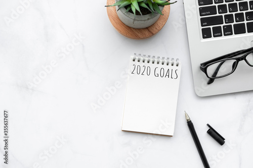 Obraz Small blank notebook with 2020 goals text is on top of white marble office desk table with office supplies. New year plan and resolutions concept. - fototapety do salonu