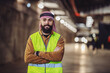 Cheerful smiling bearded arabian investor in vest, with headscarf on head standing in building in construction process with arms crossed.