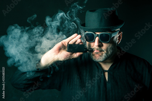 Vaper. Vaping. Man is standing in a cloud of steam. Human with a Slika na platnu