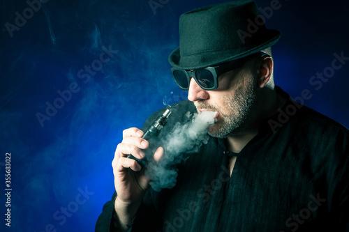 фотографія Vaper. Vaping. Man smokes a vape. Adult man with an electronic c