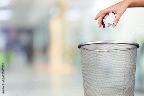 Hand throwing out paper into the trash basket Canvas Print