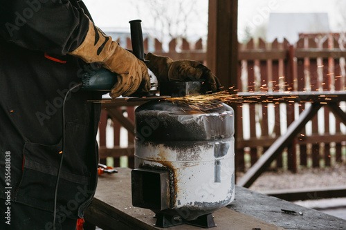 Obraz na plátně A man in a home workshop is engaged in reworking a metal product outdoor