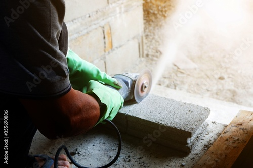 Fototapeta man bricklayer is cutting cement brick block with Small cutter machine for wall construction in new home obraz