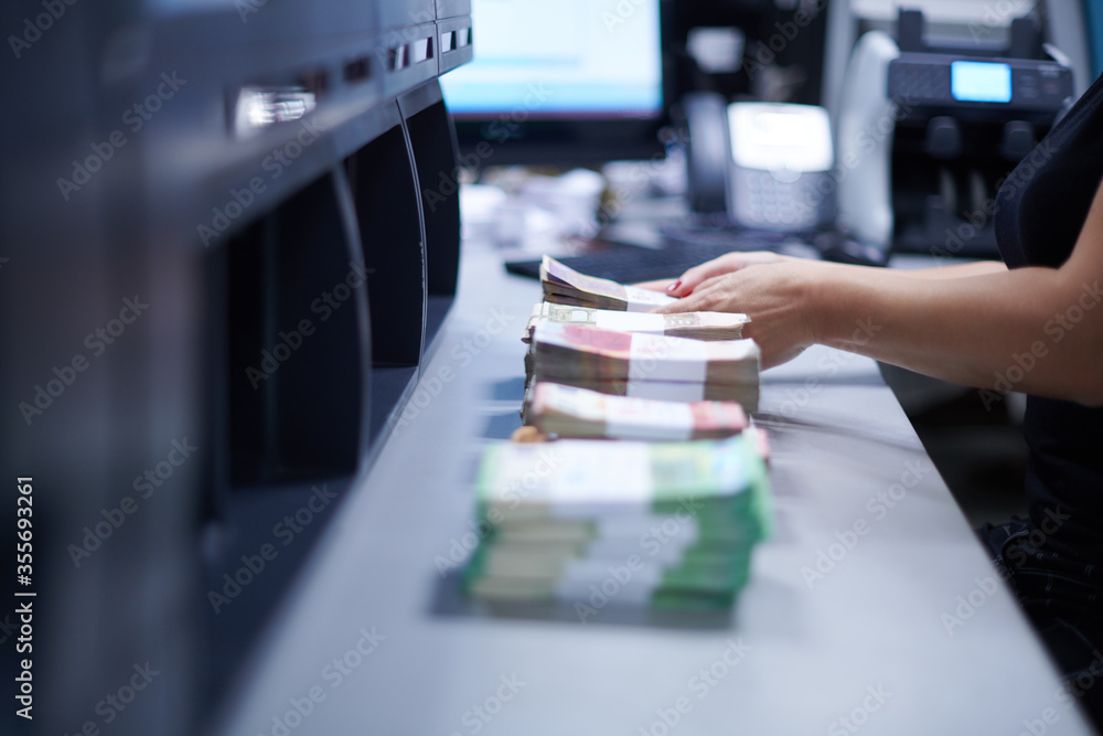 Fototapeta Bank employees sorting and counting paper banknotes