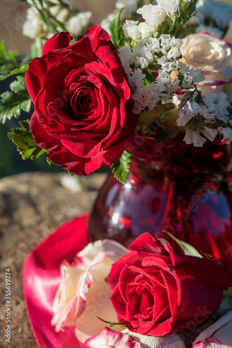red glass vase flower arrangement with large red rose amid white flowers