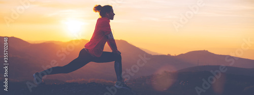 Obraz Silhouette of athletic girl doing stretching after a great jog in the mountains at sunset. Sport tight clothes. - fototapety do salonu
