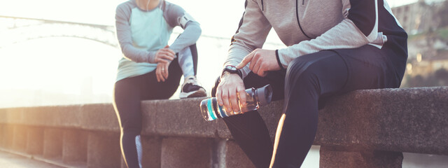 Couple of athletes resting after workout session on the street. Tired man with bottle tracking time with his arm watch and woman relaxing on the bench