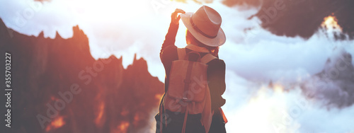 Young traveler woman wearing hat and backpack enjoying the sunset and clouds in the mountains Canvas