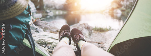 Fotografia, Obraz Young adventure woman sitting inside her camping tent with with backpack and enjoying stunning beautiful morning in mountain wilderness near the lake