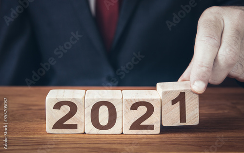 A businessman changing a calender date to 2021 and looking ahead or forward thin Canvas Print
