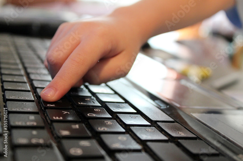 Fototapety, obrazy: Child's finger pressing a key on laptop. Close up keyboard. Kid on blurred backgound. Children in Internet. Information security