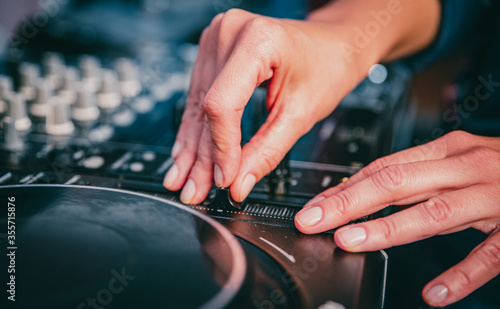 Fototapeta DJ Hands creating and regulating music on dj console mixer in concert nightclub stage. obraz