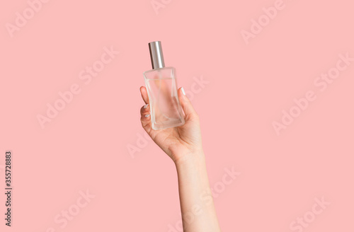 Fototapeta Cropped view of young girl holding bottle of perfume on pink background, closeup of hand obraz