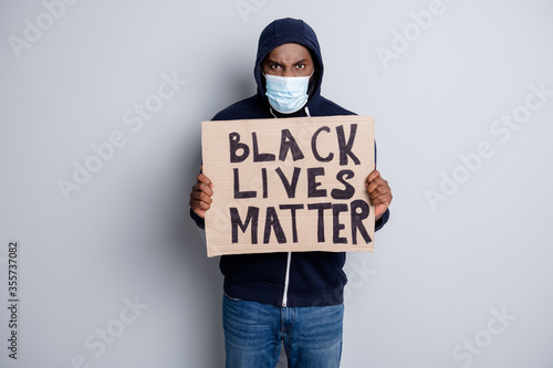 Fototapeta Save black lives. Photo of mad dark skin african poor covid infected protester hold placard stand against black citizens lawlessness wear hoodie face mask isolated grey color background obraz