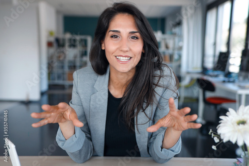 Foto Confident business woman looking and speaking through the webcam while making a video conference from the office
