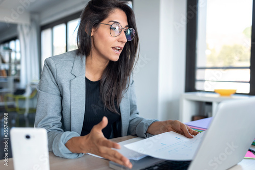 Obraz Confident business woman looking and speaking through the webcam while making a video conference with laptop from the office. - fototapety do salonu